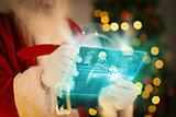 Composite image of santa using futuristic touchscreen