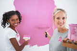 Composite image of smiling housemates painting wall pink