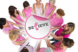 Composite image of cheerful women joined in a circle and looking at each otherwearing pink for breas