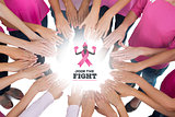 Composite image of hands joined in circle wearing pink for breast cancer