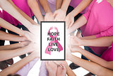 Composite image of hands joined in circle holding breast cancer struggle symbol