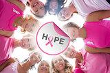 Composite image of cheerful women in circle wearing pink for breast cancer