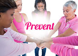 Women wearing pink and ribbons for breast cancer putting hands together