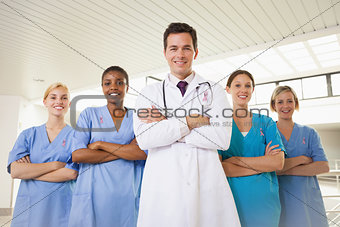 Composite image of smiling doctor and nurses with arms crossed