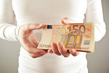 Woman holding fifty euros stack