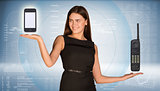 Smiling beautiful businesswoman holding two old phone and smartphone