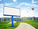 Tall buildings, green hills and road with large billboard against sky