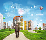 Businessman walks on road. Rear view. Buildings, grass field and sky with virtual elements