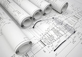 Scrolls of engineering drawings and glasses on drawing