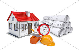Small model house with red roof near scrolls of architectural drawings and alarm clock