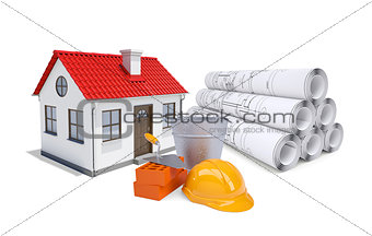 Small model house with red roof near scrolls of architectural drawings and work tools