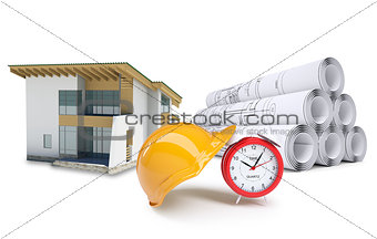 Small model house near scrolls of architectural drawings and alarm clock