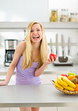 Portrait of smiling young woman with apple in modern kitchen