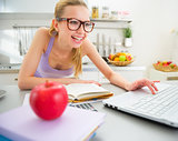 Happy young woman studying in kitchen