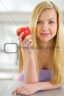 Portrait of young woman holding apple