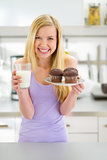 Portrait of happy teenager girl with muffin and milk in kitchen