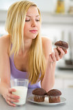 Teenager girl eating muffin with milk in kitchen