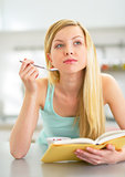 Young woman eating yogurt in kitchen and reading book