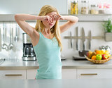 Young woman standing in in kitchen and rubbing eyes after sleep