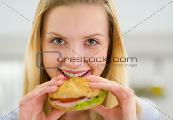 Portrait of happy young woman eating sandwich