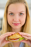 Portrait of young woman holding sandwich