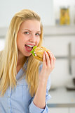 Happy young woman eating sandwich
