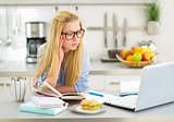 Young woman studying in kitchen