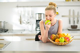 Portrait of young woman eating apple in kitchen