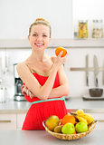 Portrait of happy young woman with fruits in kitchen