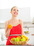 Happy young woman with fruits in kitchen
