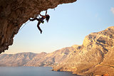 Female rock climber on overhanging cliff, Kalymnos Island