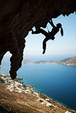 Silhouette of a young female rock climber on a cliff. Kalymnos Island