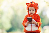 Toddler boy in fox costume holding smartphone