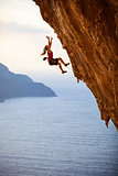 Female rock climber falling of a cliff while lead climbing