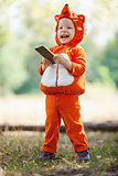 Joyful toddler boy in fox costume holding smartphone