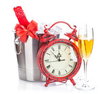 Two champagne glasses, bottle in cooler and clock
