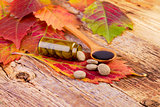 medicine bottle, pills on leaf and syrup in wooden spoon