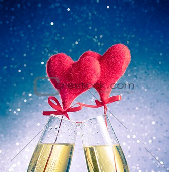 champagne flutes with golden bubbles and red velvet hearts make cheers on blue bokeh background