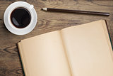Open diary and coffee cup on old wooden table top view