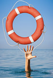 Help concept. Lifebuoy for drowning man's hand in open sea or ocean water.