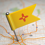 New Mexico Small Flag on a Map Background.