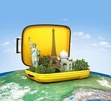 Opened suitcase with world famous monuments inside. Unusual traveling concept.
