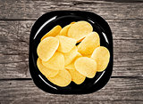 chips on a black plate on a wooden background