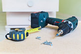 Close-up view of electric screwdriver, screws & tape ruler