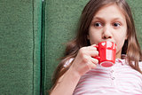 young little girl drinking from a small red cup