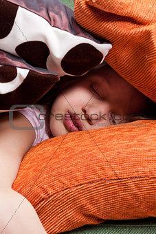 little girl asleep among a lot of pillows