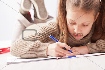 little girl drawing on her notebook
