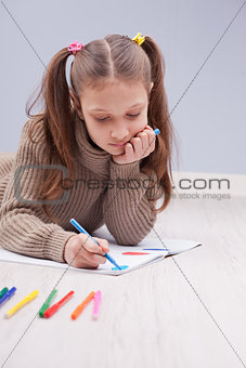 little girl colouring on her notebook