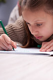 little girl writing concentrated on her exercise book