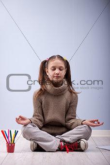 little girl meditating instead of making homework